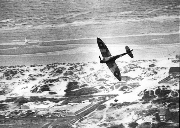 An RAF Spitfire flies over the dunes of Dunkirk 1976